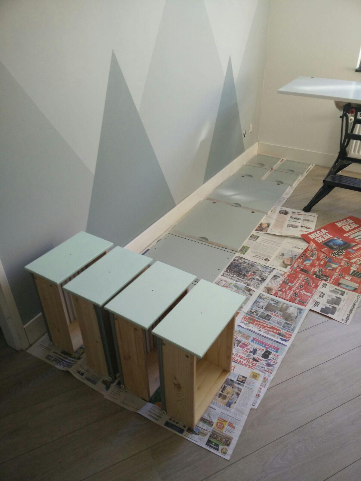 Lades van een IKEA HEMNES commode en RAKKE kledingkast liggen te drogen na een verflaag