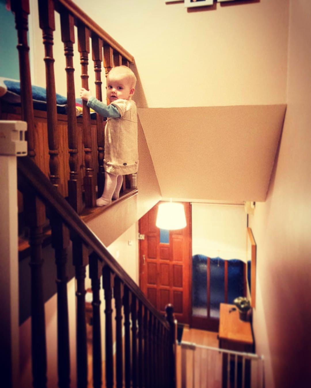 Een jong meisje is gephotoshopt op de schoot van haar vader waar door het lijkt of ze op een smal randje boven langs een trap loopt.