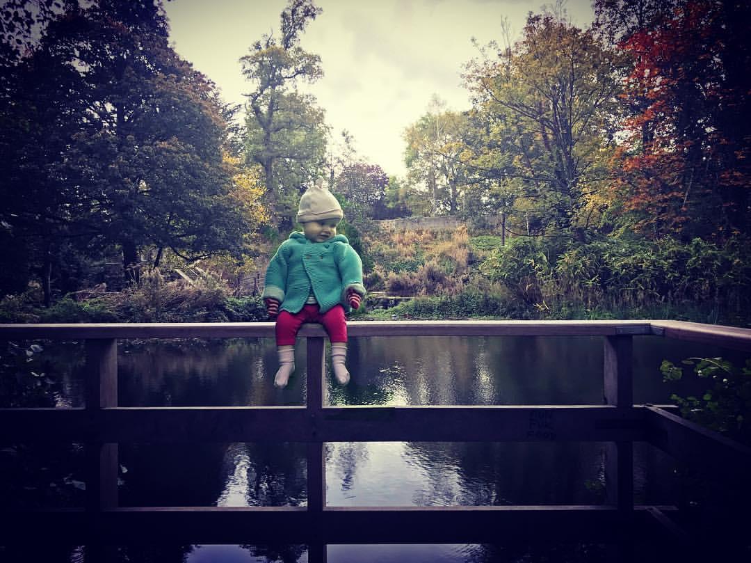Een jong meisje is gephotoshopt op de schoot van haar vader waar door het lijkt of ze zonder ondersteuning op een hekje boven het water zit