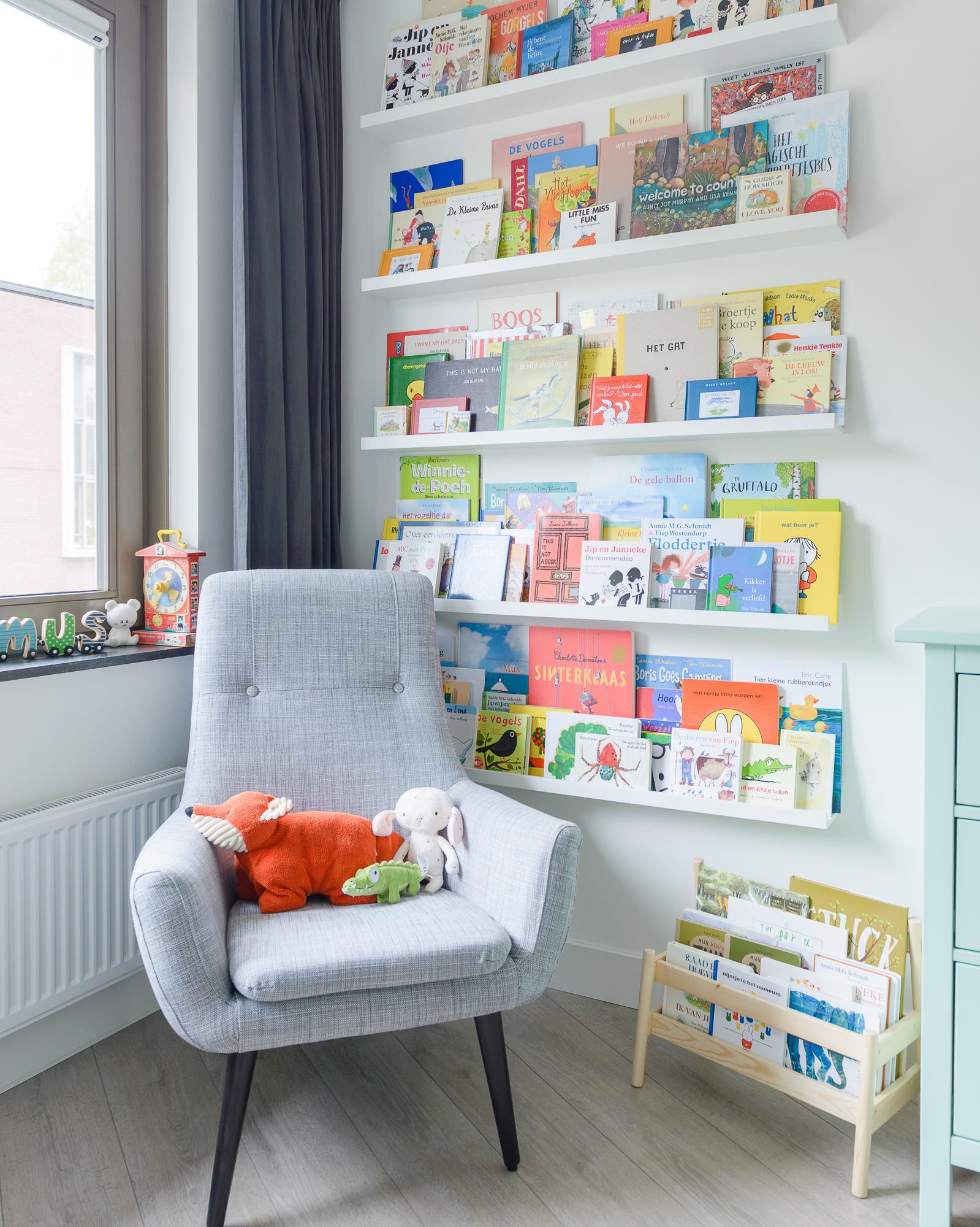 Een hoek van een kinderkamer met planken vol kinderboeken