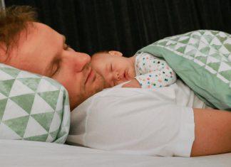 Een vader met zijn baby die op hem slaapt